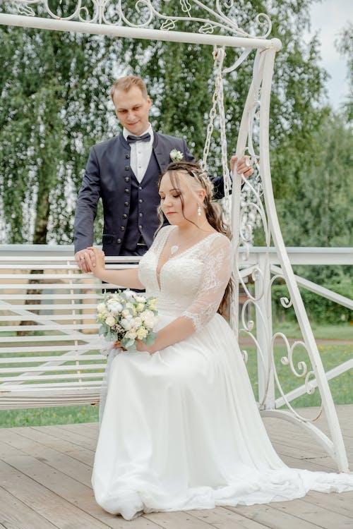 Groom Standing Behind Bride Sitting on Swings and Holding Hands