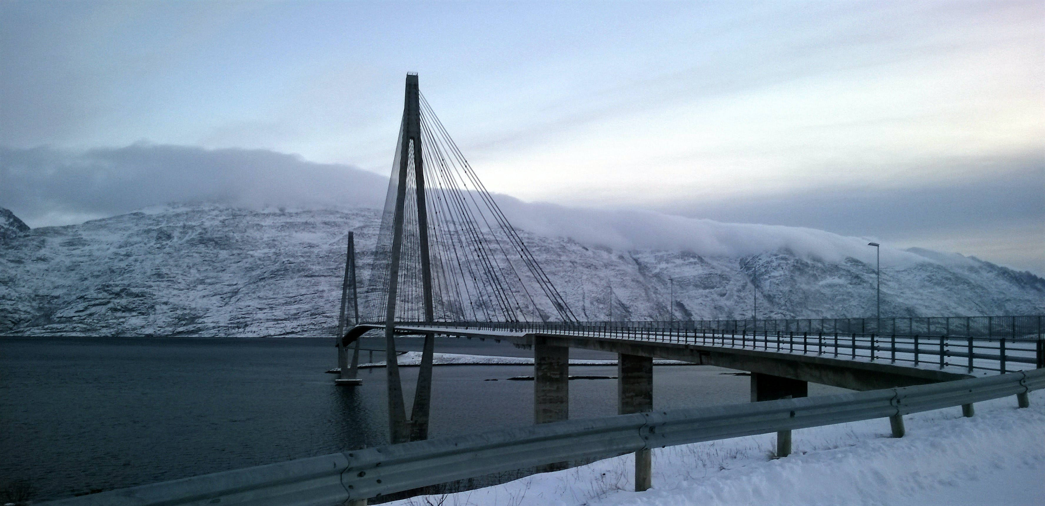 Black Suspension Bridge Under Cumulus Clouds