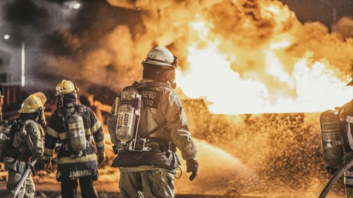 Firefighters Standing in Front of Flame