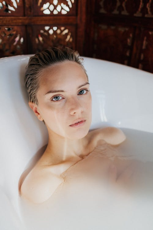 Woman in White Bathtub With Water