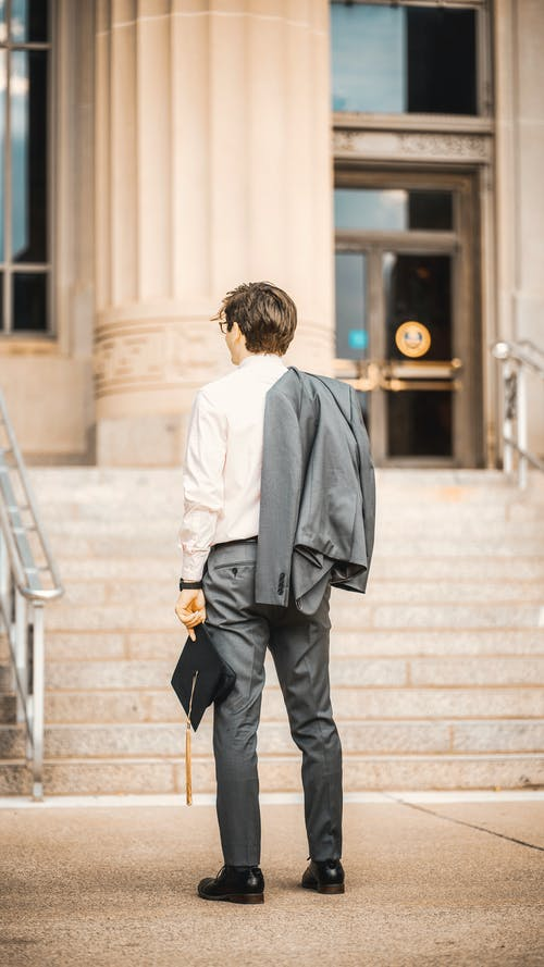 Boy in White Dress Shirt and Black Pants Standing on Stairs