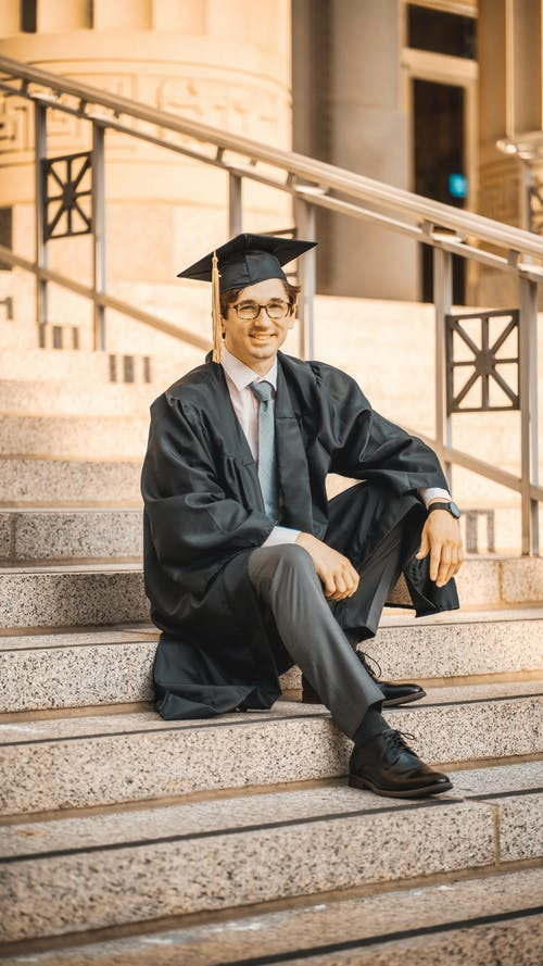 Man in Black Academic Dress Sitting on Stairs