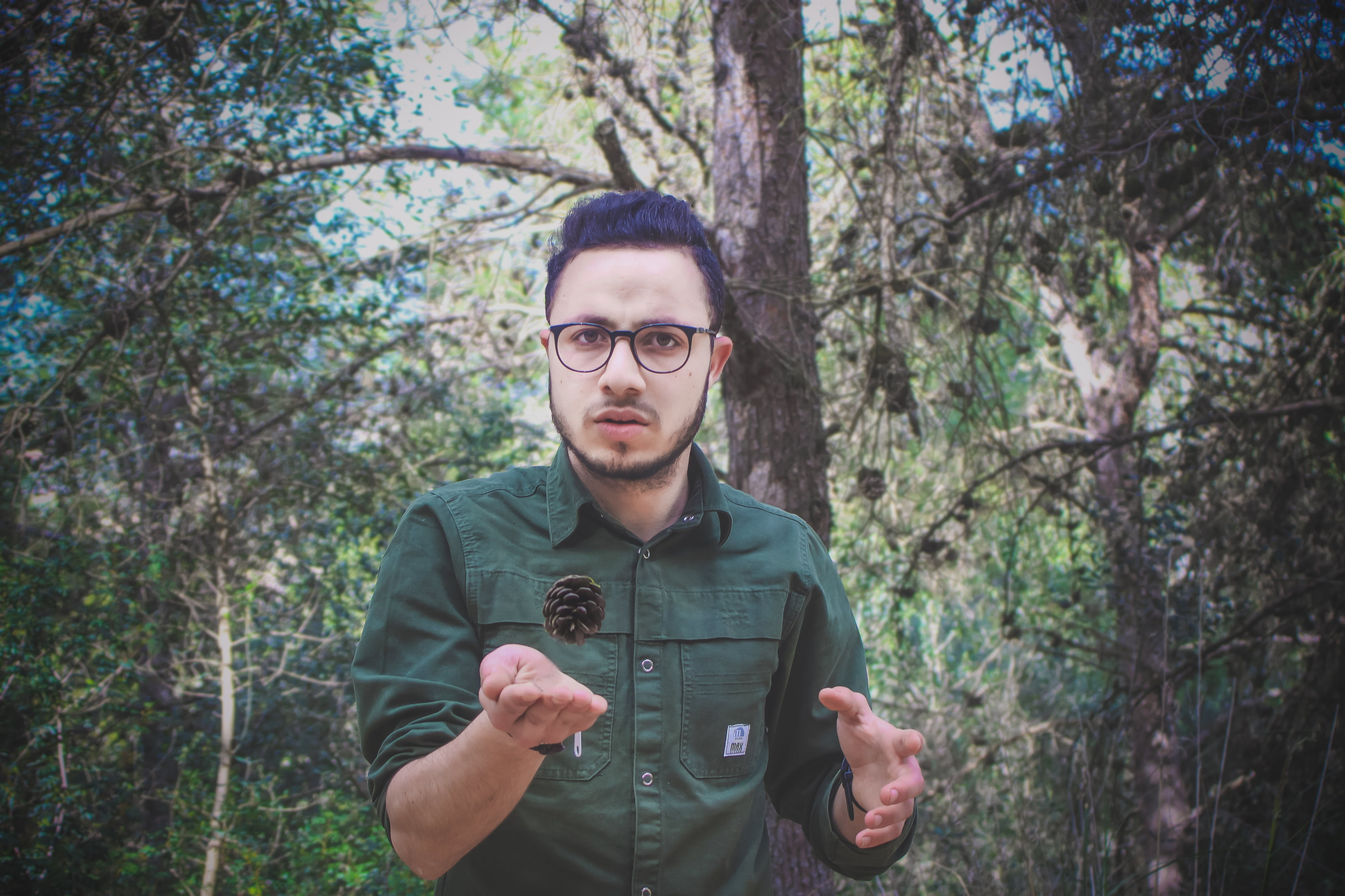 Man Wearing Green Dress Shirt and Surrounded by Trees