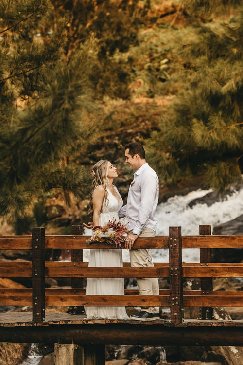 Man and Woman Sitting on Brown Wooden Fence