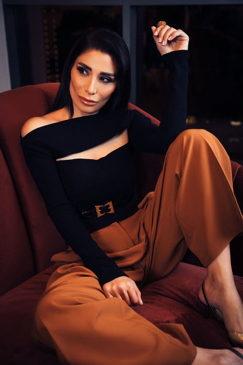 Woman in Black Long Sleeve Shirt and Brown Pants Sitting on Brown Couch