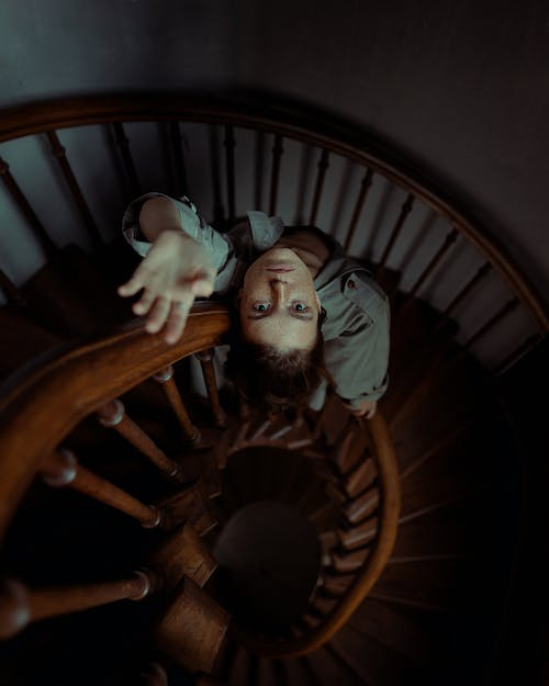 Baby in White Onesie on Brown Wooden Spiral Staircase