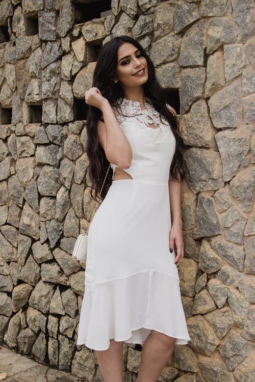 Woman in White Dress Leaning on Brick Wall Posing for Photo
