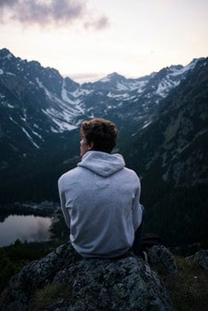 Man Wearing White Hoodie Sitting on a Rock With a View on Mountain