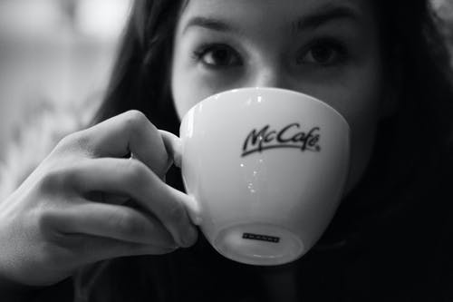 Grayscale Photography of Woman Drinking Coffee