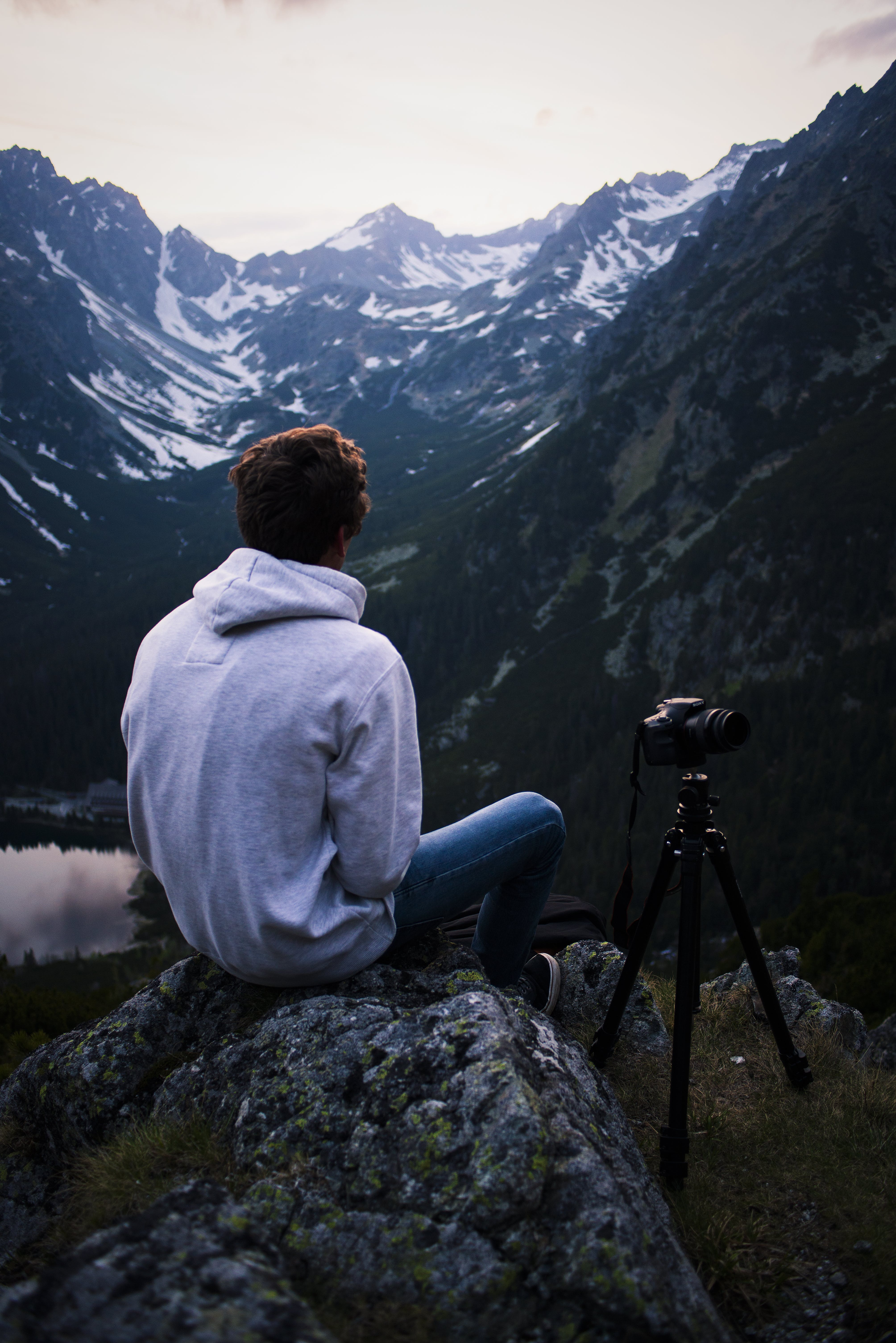 Man in Gray Hoodie Sitting on Gray Stone With Dslr Camera Tripod
