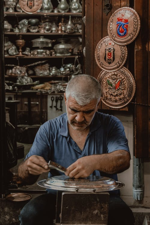 Man in Blue Polo Shirt Doing Metal Crafting