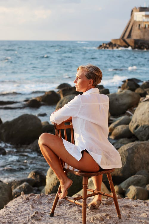 Woman in White Long Sleeve Shirt Sitting on Brown Wooden Chair on Beach