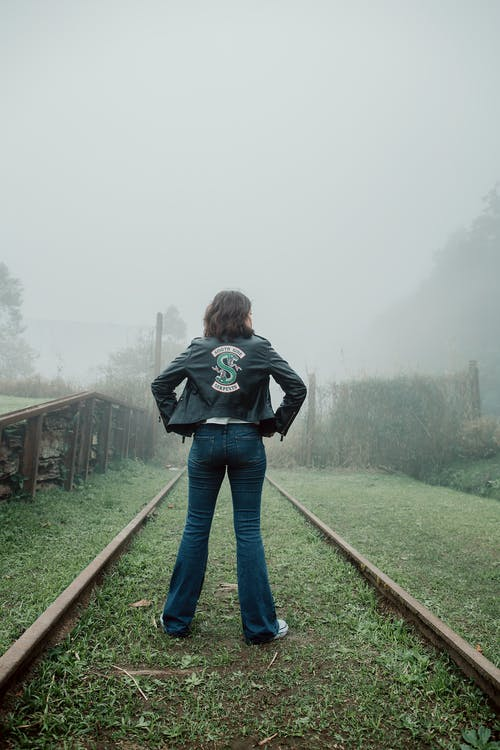 Woman in Black Jacket and Blue Denim Jeans Standing on Railway On A Foggy Day