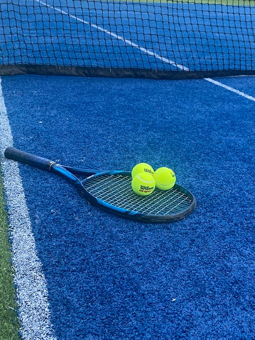 Blue Tennis Racket and Balls on Blue Clay Court