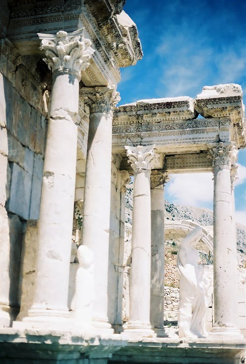 Ancient Structure Of Pillars and Statue Under Blue Sky
