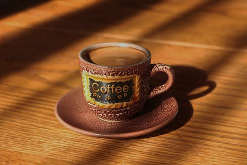 Ceramic Cup of Coffee with Saucer on a  Wooden Table top