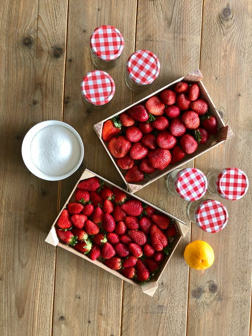 Strawberries and Glass Jars on a Wooden Table
