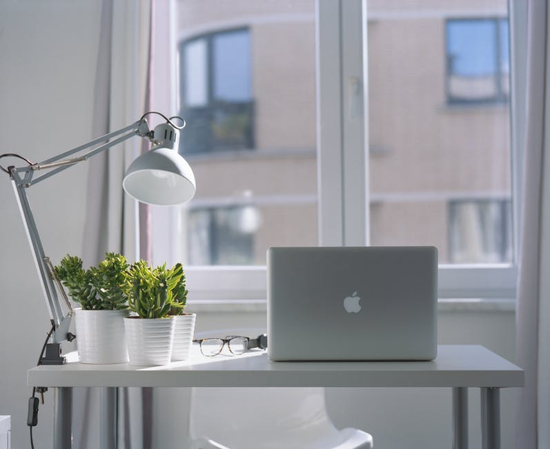 Silver Macbook Air and Goose Neck Lamp