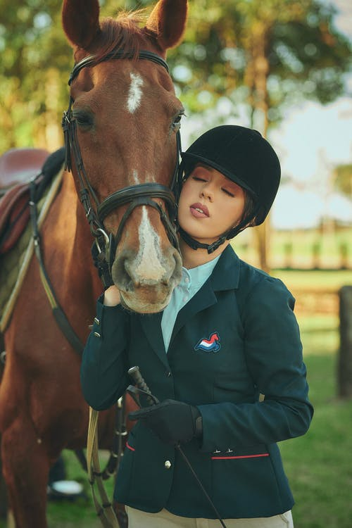 Girl in Black Coat Riding Brown Horse