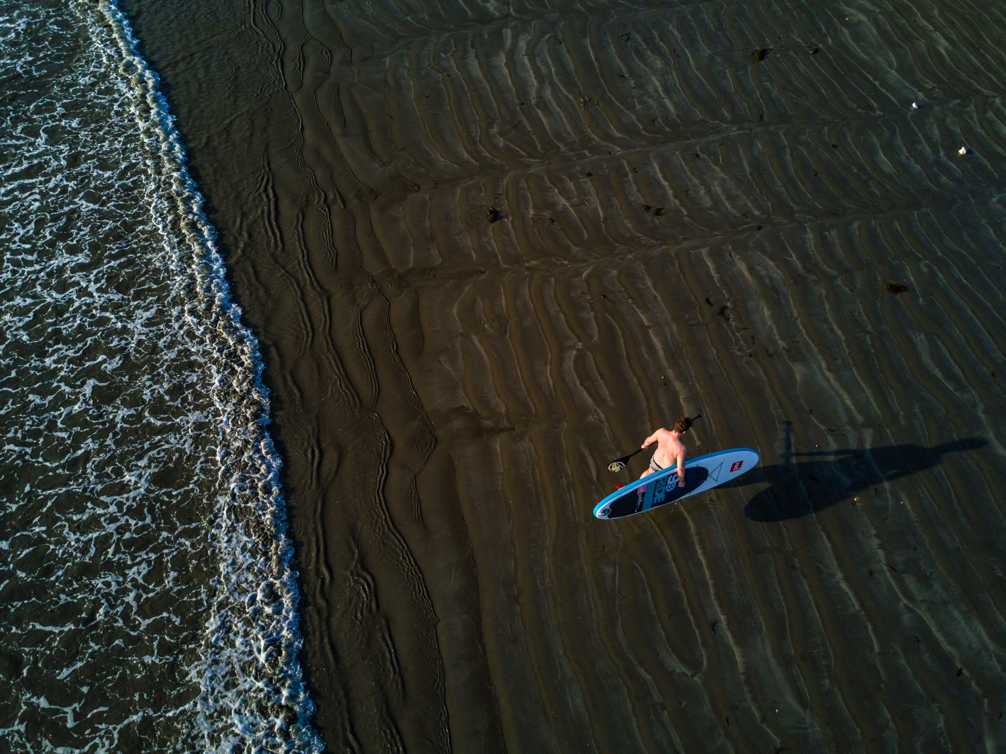 Person Holding Surfboard Near Seashore