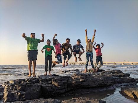Boy Wearing Green Crew-neck Shirt Jumping from Black Stone on Seashore