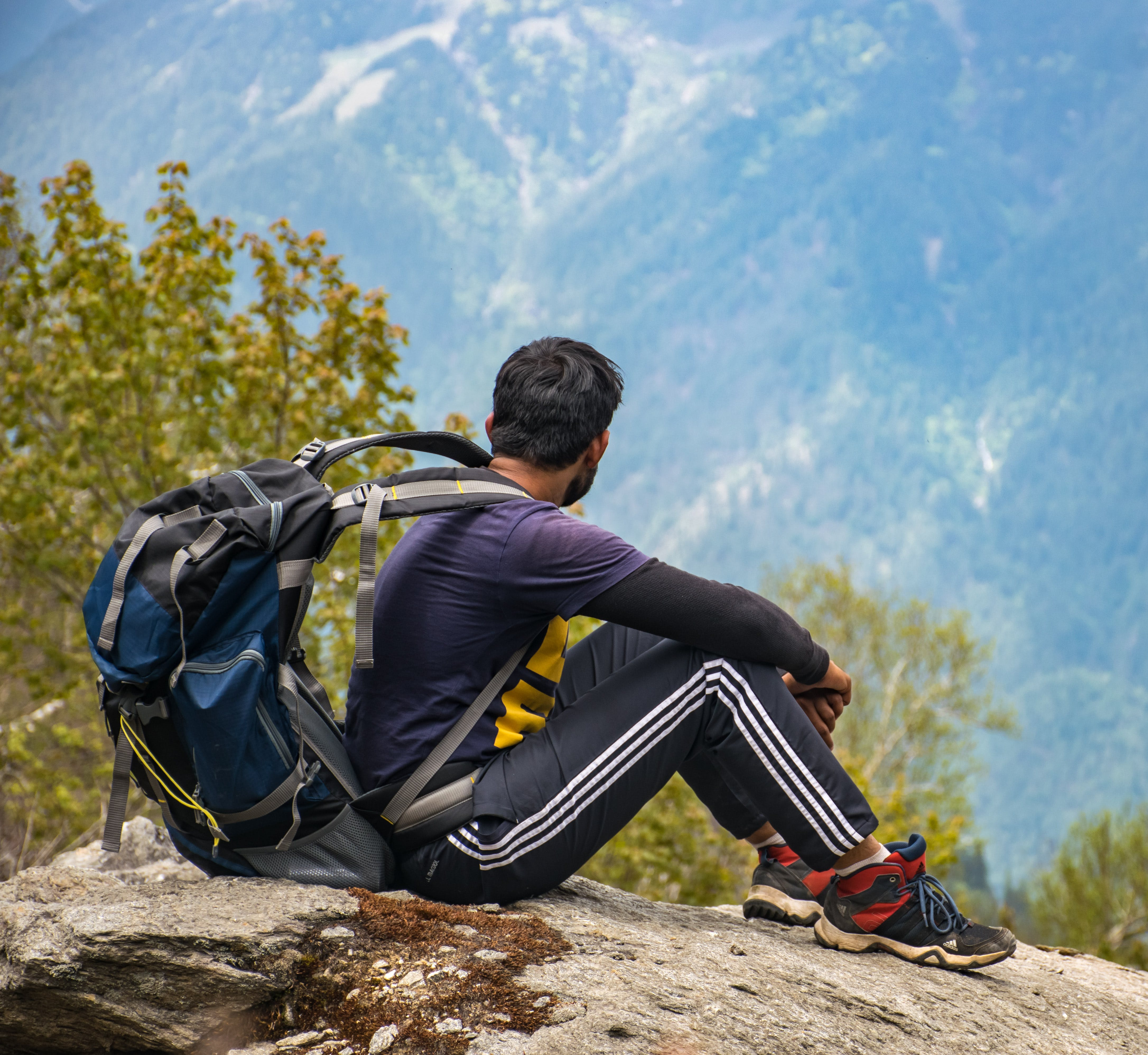 Man in Purple T-shirt With Blue Backpack Sitting on Gray Boulder