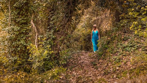 Woman Wearing Blue Jumpsuit Walking in Forest