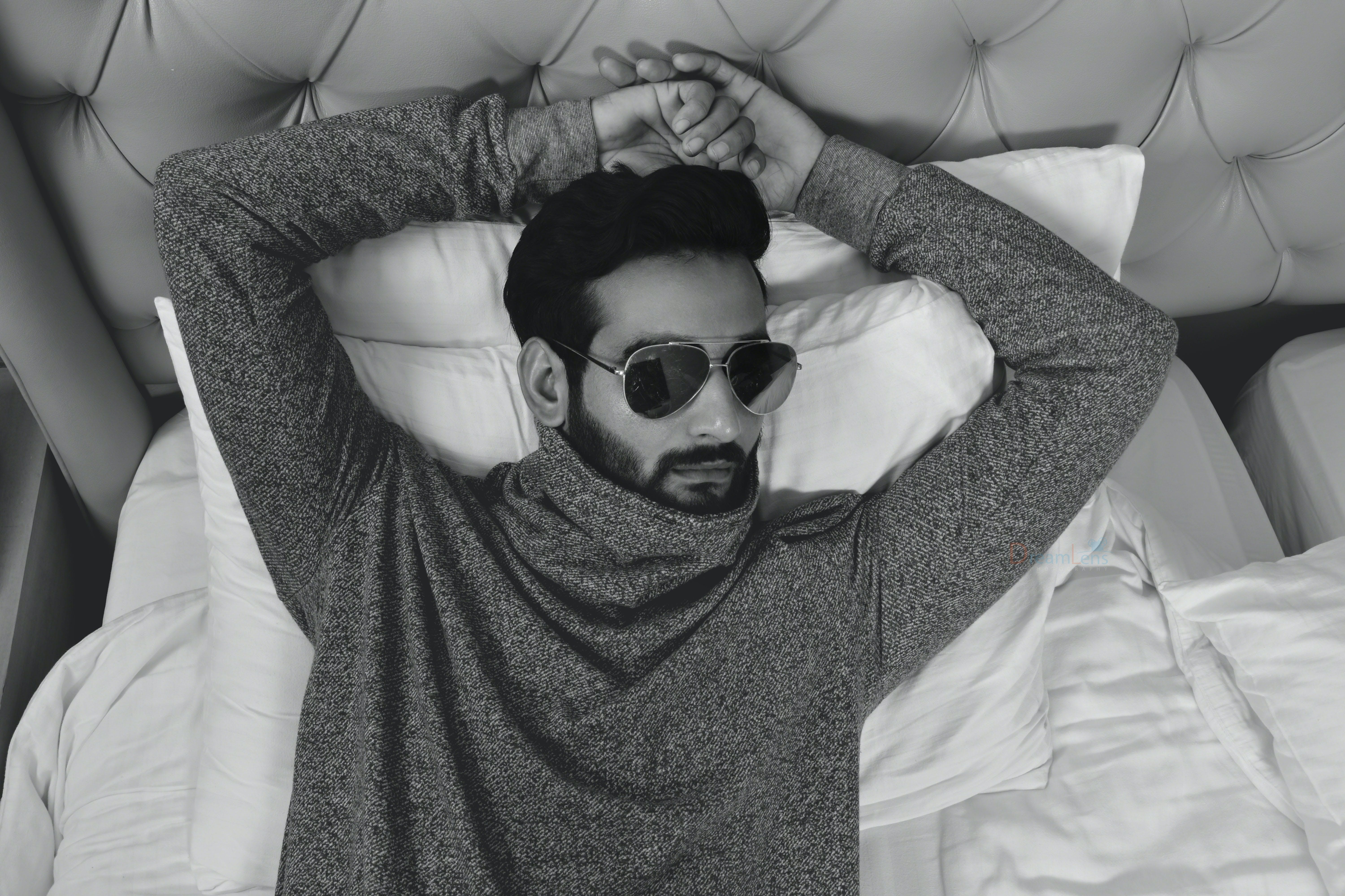 Grayscale Photo of Man in Long-sleeved Wearing Sunglasses Lying on Bed With Both Hand on Head