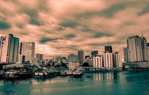 Immagine gratuita di arancia, azzurro, cieli nuvolosi, edifici