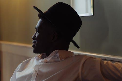 Man in White Button Up Shirt Wearing Black Hat