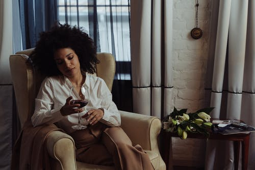 Woman in White Long Sleeve Shirt and Brown Pants Sitting on White Sofa Chair