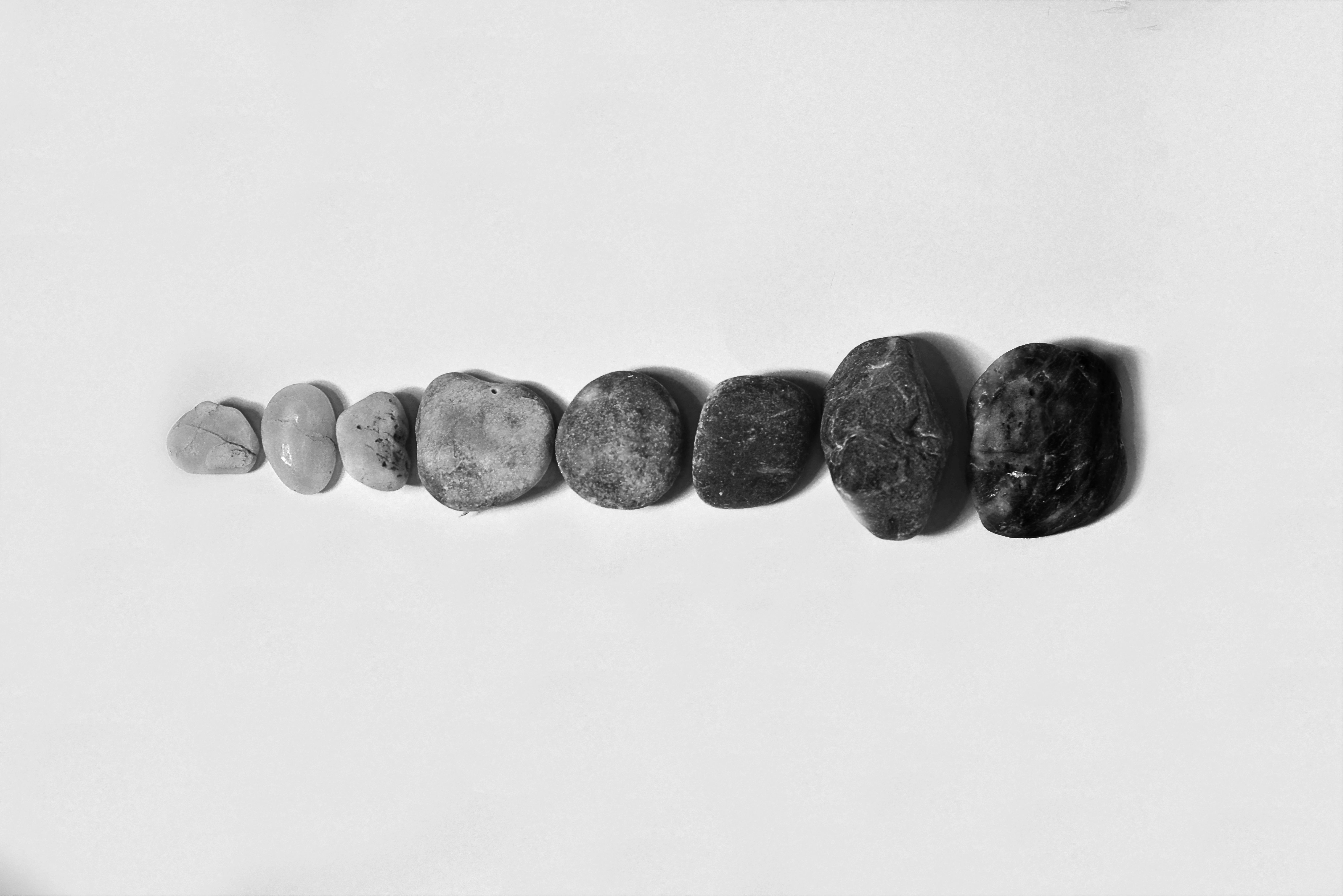 Row of Black and Gray Polished Pebble on Gray Surface