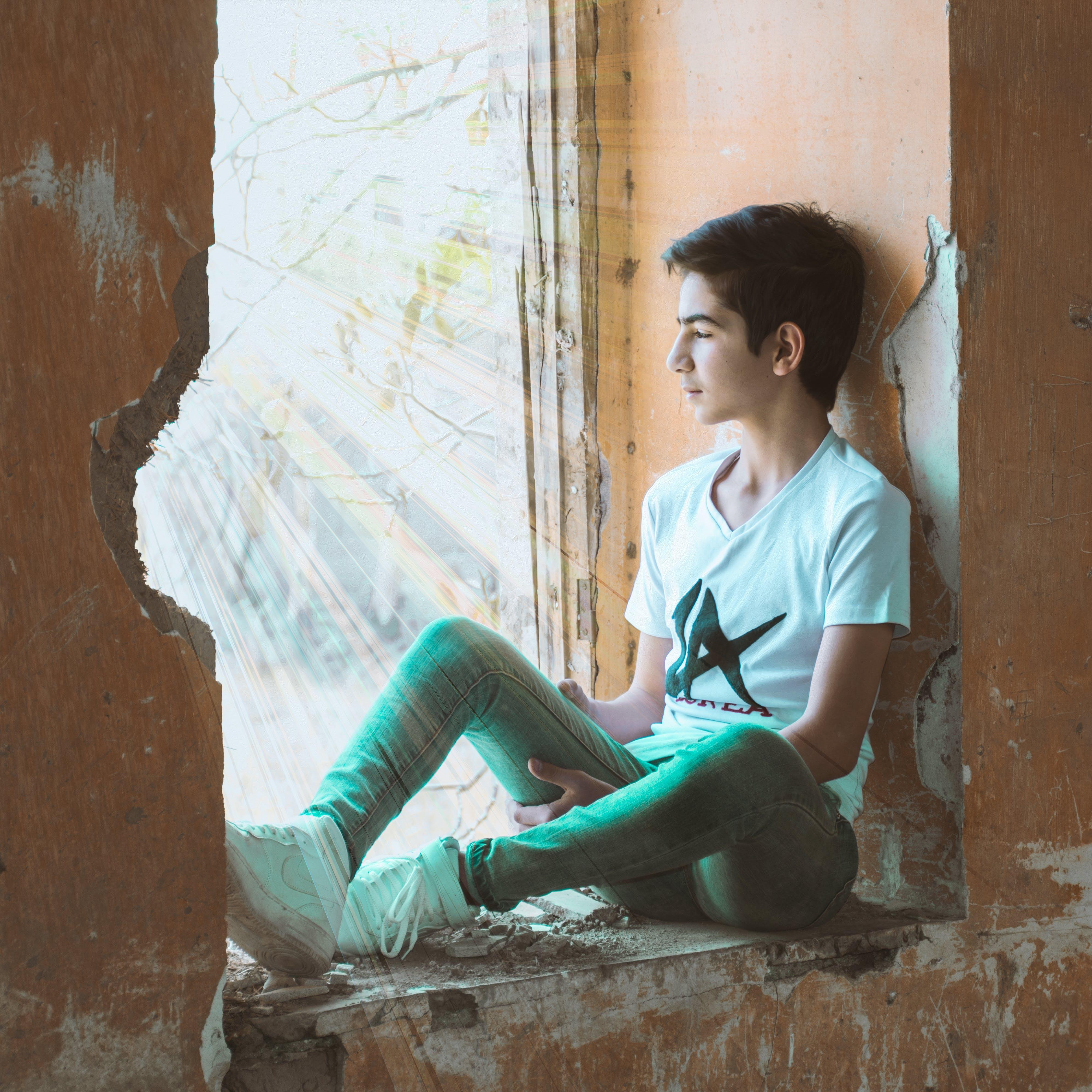 Boy Sitting Near Wall