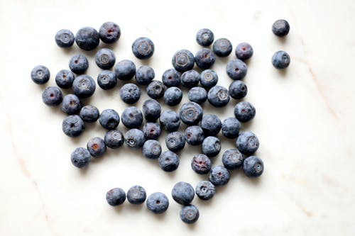 Photo of Black Berries on White Surface
