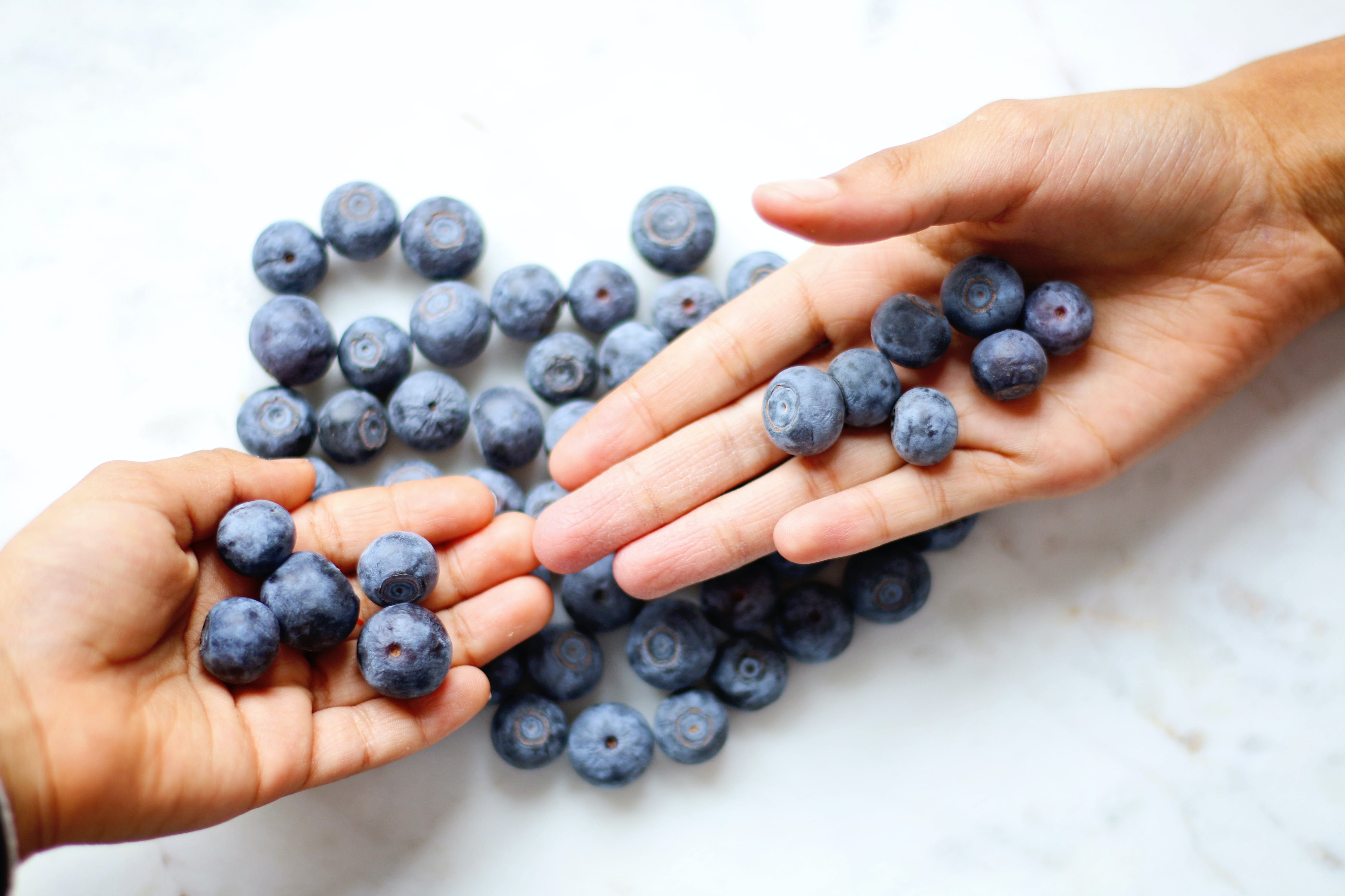 Two Person's Hand With Blueberries on Top