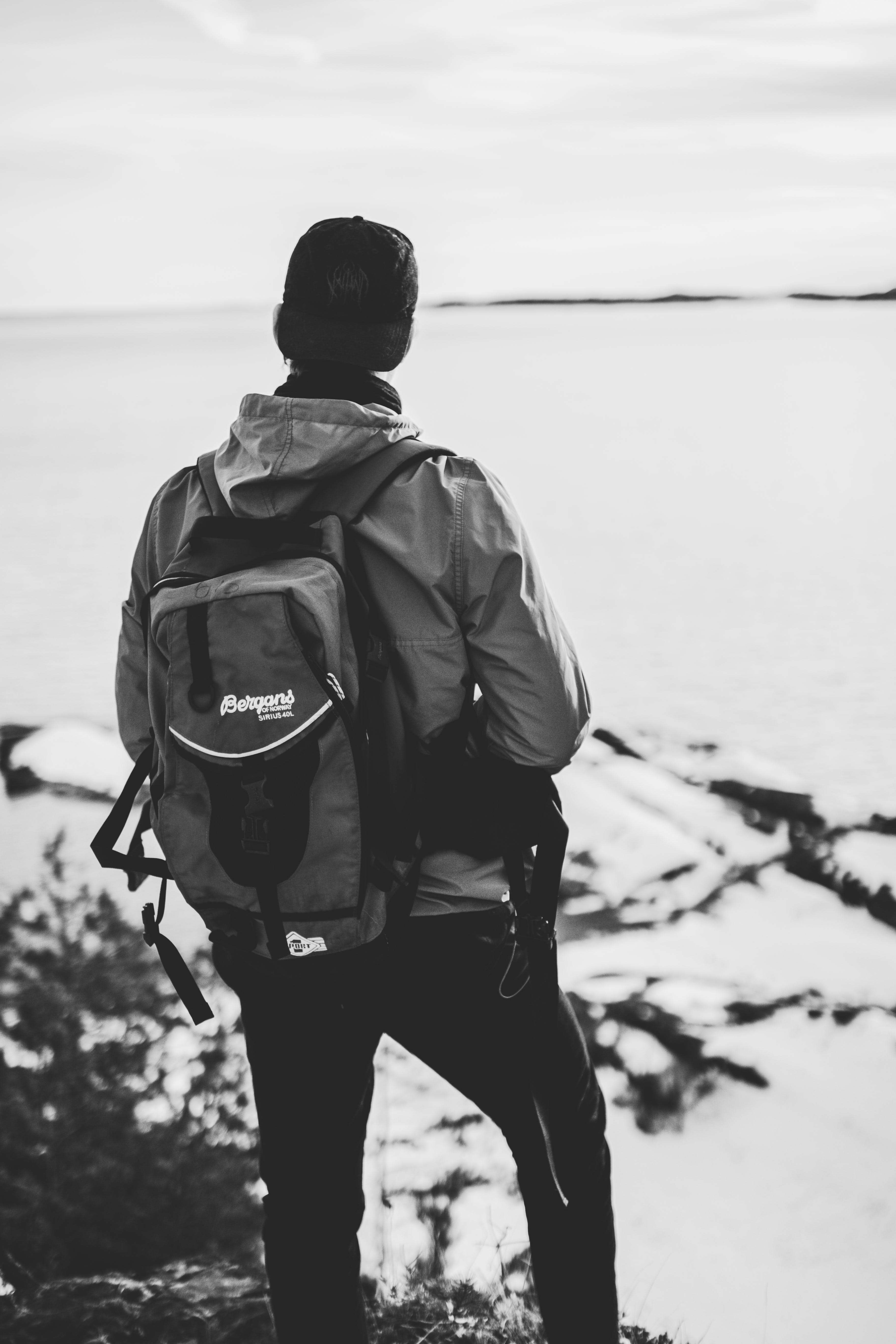 Grayscale Photo of Man Wearing Windsor and Backpack