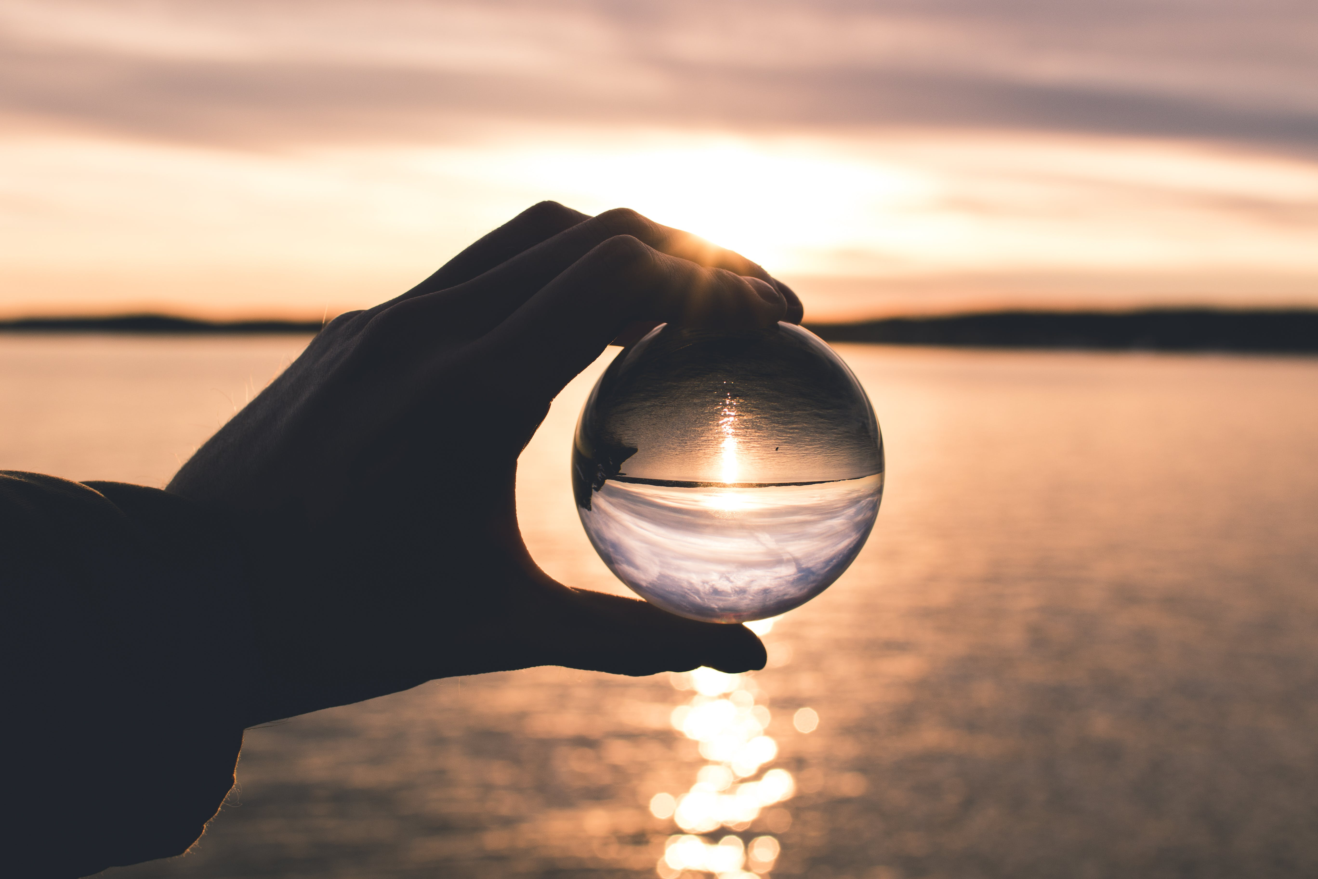 Photo Displays Person Holding Ball With Reflection of Horizon