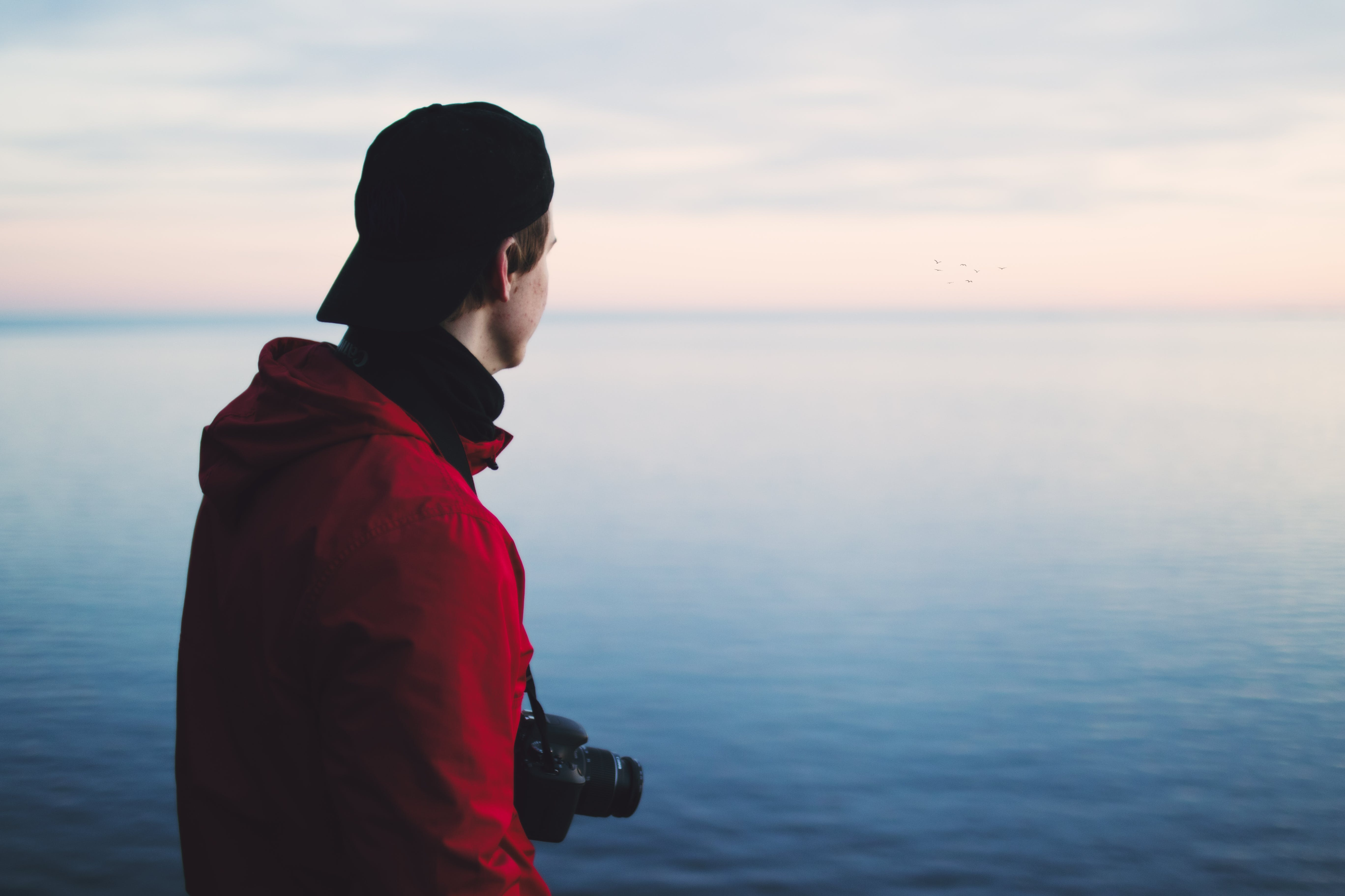 Man in Red Jacket Standing Near Body of Water