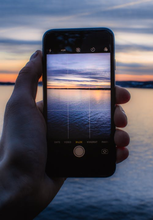 Person Holding Post-2014 Iphone Taking a Photo of Body of Water