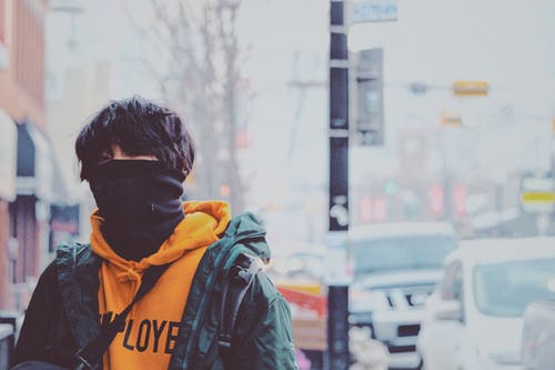 Man in Orange Pullover Hoodie and Green Jacket Covered With Black Mask