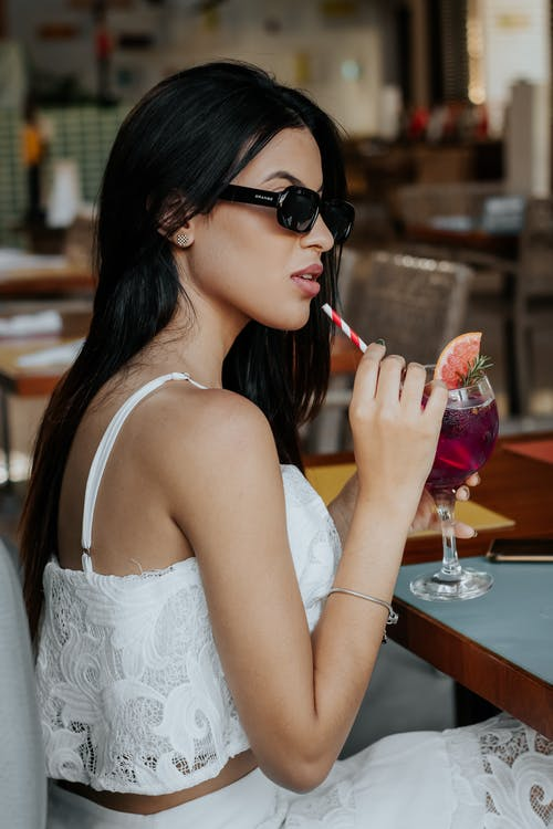 Woman in White Spaghetti Strap Dress Holding Clear Wine Glass