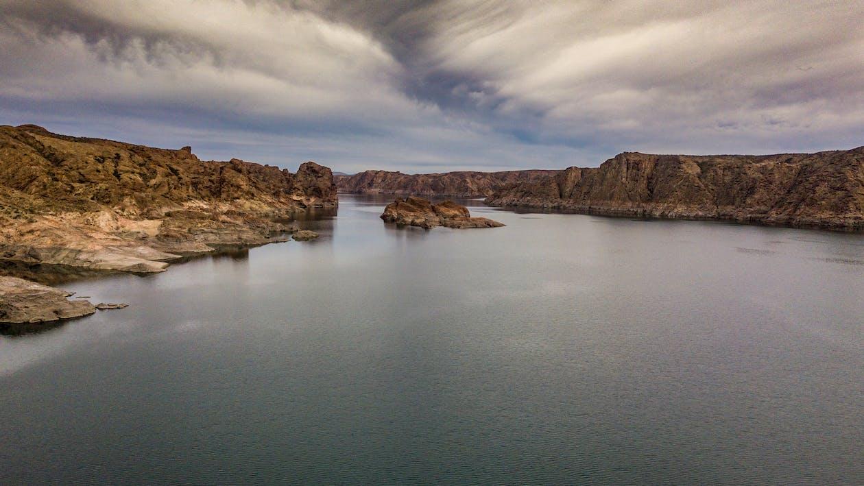 Brown Rocky Mountain Beside Body of Water Under Blue Sky