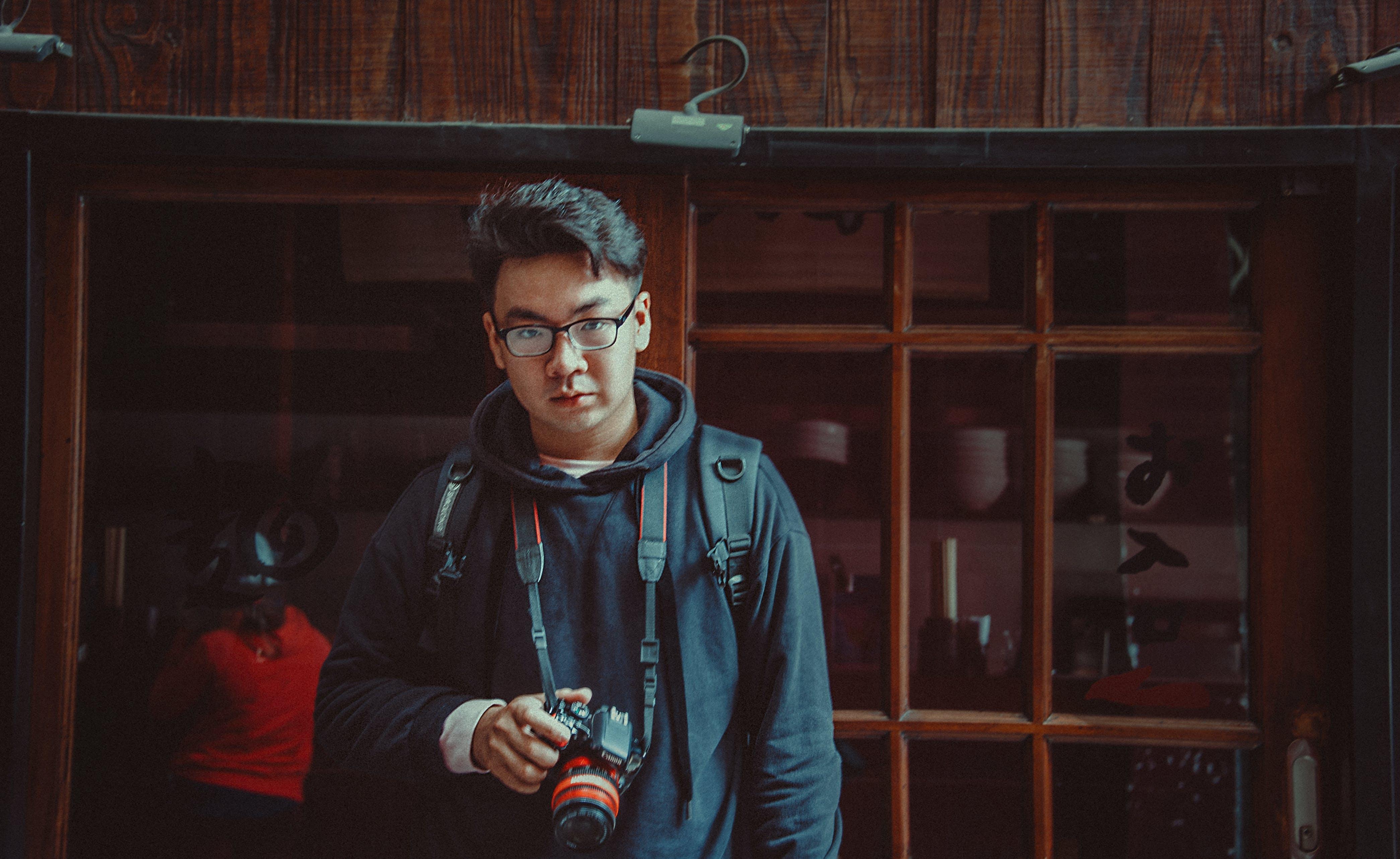 Man Wearing Jacket Holding Dslr Camera