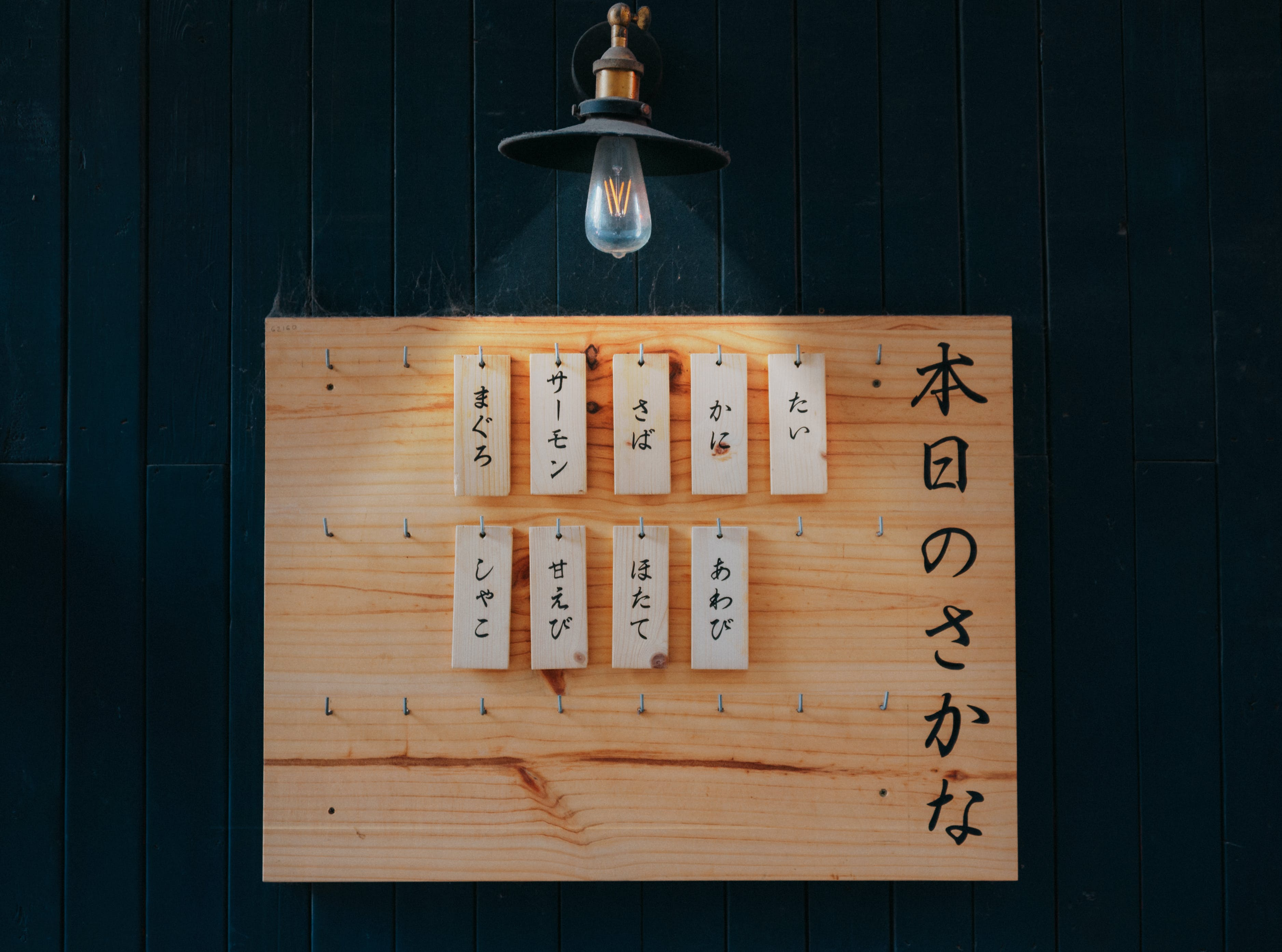 Kanji Printed Tags Hanged on Brown Wooden Board Lighted by Pendant Lamp