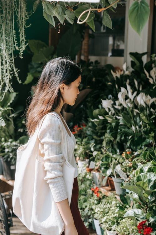 A Woman Looking at Plants on Display