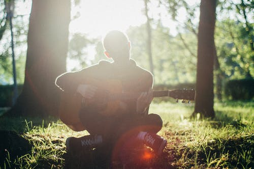 Man Siting on Grass While Playing Guitar