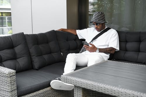 Man in White Shirt and Pants Sitting on the Sofa
