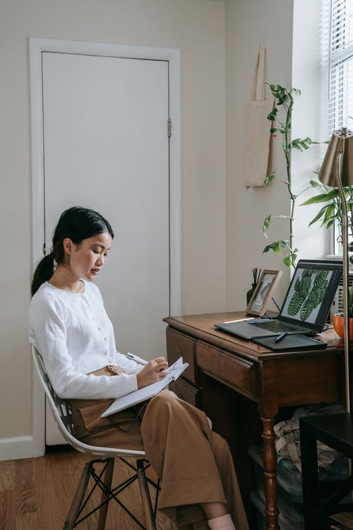 Woman in White Long Sleeve Shirt Sitting on Chair in Front of Laptop Computer