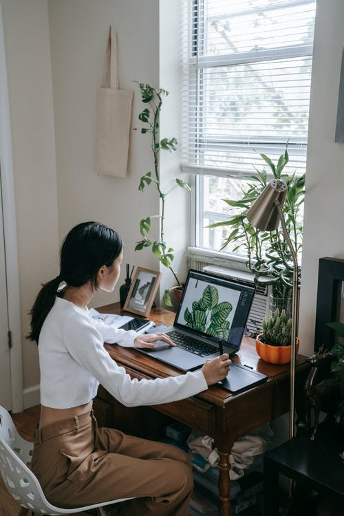 Woman in White Long Sleeve Shirt Using Macbook Air on Brown Wooden Desk