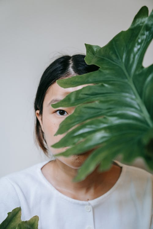 Woman in White Crew Neck Shirt Covering Her Face With Green Leaves